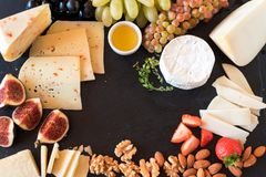 Tasting cheese dish with fruits, berries on old black cheeseboard. Food for wine and romantic, cheese delicatessen. Menu design ho. Tasting cheese dish with Stock Photos