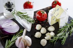Tasting cheese dish with tomatos on old black dask. Food for wine and romantic, cheese delicatessen. Menu design horizontal royalty free stock photography