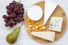 Tasting cheese with fruits on a white wooden background. Food for wine, top view. Flat lay. From above Stock Image