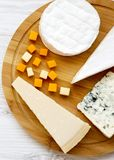 Tasting cheese on round bamboo board on a white wooden table. Food for wine, top view. Flat lay, from above, overhead. Tasting cheese on round bamboo board on a royalty free stock image