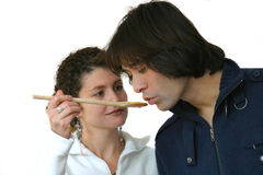 Tasting the cooking. Attractive young couple tasting from a spoon on white background Stock Photos