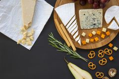 Tasting different types of cheeses with fruits, pretzels walnuts and bread sticks on dark background. Food for wine, romantic. Top view stock image