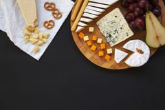 Tasting different types of cheeses with fruits, pretzels walnuts and bread sticks on dark background. Food for wine, romantic. Copy space. Top view stock images