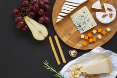 Tasting different types of cheeses with fruits, pretzels walnuts and bread sticks on dark background. Food for wine, romantic. Top view royalty free stock photos