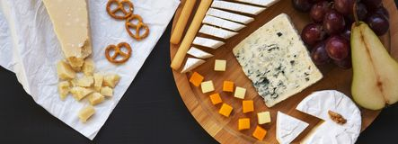 Tasting different types of cheeses with fruits, pretzels walnuts and bread sticks on dark surface, overhead. Food for wine. Top. View, flat lay stock photos