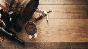 Tasting excellent red wine. Excellent red wine bottles, wineglass, barrel and corkscrew on a rustic wooden table: traditional winemaking and wine tasting concept Stock Photography