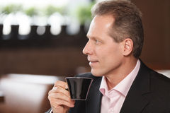 Tasting a fresh coffee. Cheerful mature men in formalwear drinki. Tasting a fresh coffee. Cheerful mature man in formalwear drinking coffee at restaurant Royalty Free Stock Photos