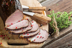 Tasting fresh piece of ham in a smokehouse Stock Image
