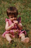 Tasting my dress. A little girl,siting in the grass ,day light Royalty Free Stock Photography