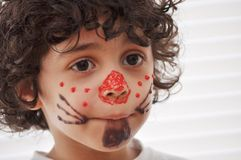 Latin child tasting his candy made mask during a b. Hispanic child having fun in a friends birthday, boy with beautiful curly hair tasting his syrup made mask Stock Photography