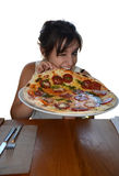 Tasting pizza. Young cute woman tasting a big pizza stock image
