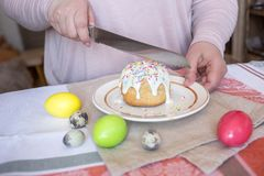Tasting a traditional Easter cake, a woman cuts a cake with a knife. Colored eggs on a table stock photos