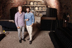 Tasting wine. Portrait of senior winemaker and young sommelier standing in wine cellar and tasting wine Stock Images