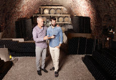Tasting wine. Portrait of senior winemaker and young sommelier standing in wine cellar and tasting wine Royalty Free Stock Photos