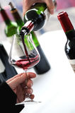 Tasting wine in a vinery. A man`s hand is pouring red wine into a glass with a corkscrew set down. Lot of wine bottles in the background with shadows Stock Image
