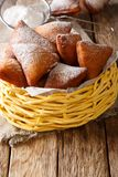Tasty African Mandazi with powdered sugar close-up in a basket. Tasty African Mandazi with powdered sugar close-up in a basket on the table. vertical royalty free stock images