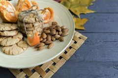Tasty almond cookies on a wooden plate surrounded by autumn. Leaves Royalty Free Stock Photos