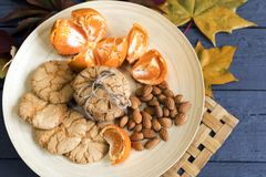 Tasty almond cookies on a wooden plate surrounded by autumn. Leaves Royalty Free Stock Photo