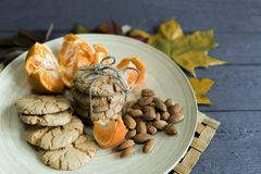 Tasty almond cookies on a wooden plate surrounded by autumn. Leaves Stock Photography