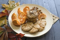 Tasty almond cookies on a wooden plate surrounded. By autumn leaves Stock Images