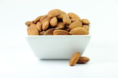 Tasty almonds nuts in white dish. Isolated on white background Royalty Free Stock Photo