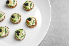 Tasty appetizer with black caviar and cucumber Royalty Free Stock Images