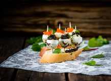 Tasty appetizer of quail eggs with red and black caviar. Stock Photos