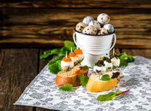 Tasty appetizer of quail eggs with red and black caviar. Stock Photo