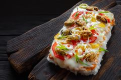 Tasty appetizing asian food. Delicious japanese rice pizza with. Mussels served on rustic wooden table Stock Photography
