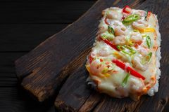 Tasty appetizing asian food. Delicious japanese rice pizza with. Shrimps served on rustic wooden table Royalty Free Stock Photo