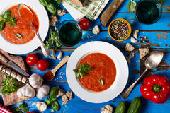Tasty appetizing classic spanish soup gazpacho in white plates o. N rustic blue table with bread, garlic and spices. Dinner Food Concept. Top View Stock Images