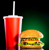 Tasty and appetizing hamburger on a darkly green. Background Stock Photos