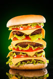 Tasty and appetizing hamburger on a darkly green. Background Royalty Free Stock Photos