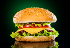 Tasty and appetizing hamburger on a darkly green. Background Royalty Free Stock Photography