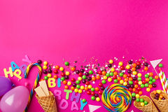 Tasty appetizing Party Accessories on Bright Pink Background. Tasty appetizing Party Accessories Happy Birthday Sweet Treat Swirl Balloon Candy Lollypop Colorful Royalty Free Stock Photography