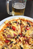 Tasty appetizing pizza and glass of beer Royalty Free Stock Photos