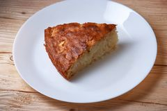 Tasty apple pie slice on white plate. And wooden table Stock Images