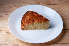 Tasty apple pie slice on white plate. And wooden table Royalty Free Stock Photos