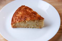 Tasty apple pie slice on white plate. And wooden table Royalty Free Stock Photography
