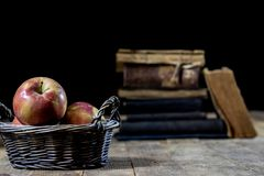 Tasty apples in basket on kitchen table. Old books lie next to a Stock Images