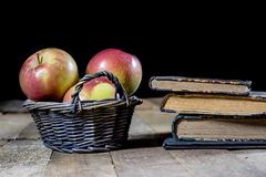 Tasty apples in basket on kitchen table. Old books lie next to a Royalty Free Stock Image