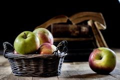 Tasty apples in basket on kitchen table. Old books lie next to a Stock Photo