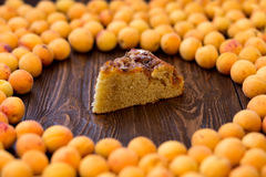 Tasty apricot pie on wooden background, cut a piece of cake stock photos