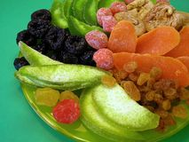 Tasty colorful dried fruits in green plate stock photo