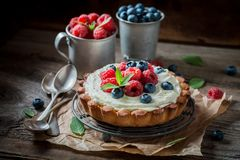 Tasty and aromatic tart with mascarpone cheese and fruit. On old wooden table royalty free stock image