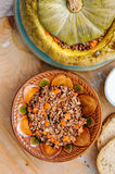 Tasty autumn stuffed pumpkin with buckweat and mushrooms. On rustic wooden table royalty free stock photography
