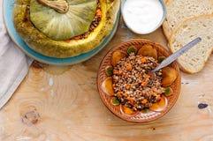 Tasty autumn stuffed pumpkin with buckweat and mushrooms. On rustic wooden table stock photo