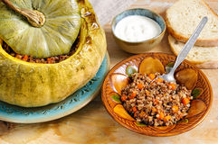 Tasty autumn stuffed pumpkin with buckweat and mushrooms. On rustic wooden table stock images