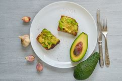 Tasty avocado toasts on the white plate with black salt and garlic ready to eat. Avocado sandwiches on the gray background royalty free stock images