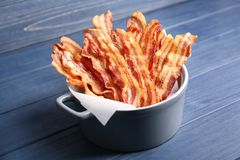 Tasty bacon slices in pan. On table Royalty Free Stock Photos